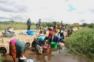 Washing clothes in a stream, Mchinji District, Malawi. Goal-setting can lift millions of people out of poverty, empower women and girls, improve health and well-being, and provide vast new opportunities for better lives. Credit: Claire Ngozo/IPS
