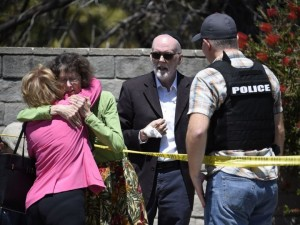 April 27, 2019, file photo, two people hug as another talks to a San Diego County Sheriff's deputy outside of the Chabad of Poway synagogue, in Poway, Calif., after a man opened fire inside as worshippers celebrated the last day of a major Jewish holiday. A Jewish civil rights group says anti-Semitic attacks in the U.S. remained near a record-high level in 2018, partially fueled by a sharp increase in physical assaults.
